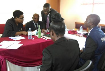 L-R-Justice-Damalie-Lwanga-HW-and-PRSA-Mbarara-consult-the-Constitution-during-the-Joint-Stakeholders-Meeting-in-Mbarara-Main-Prison-on-26-Nov-2014-1024x574